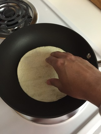 Place tortilla on hot pan to warm up one side...